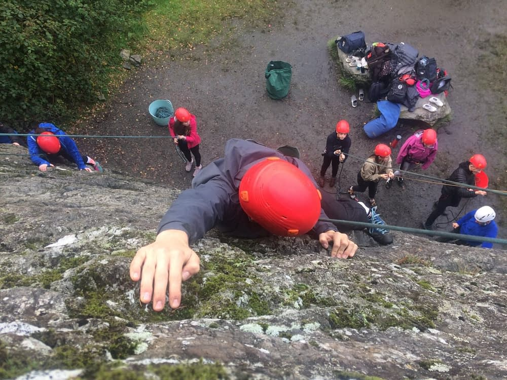 climber reaching top of cliff from above