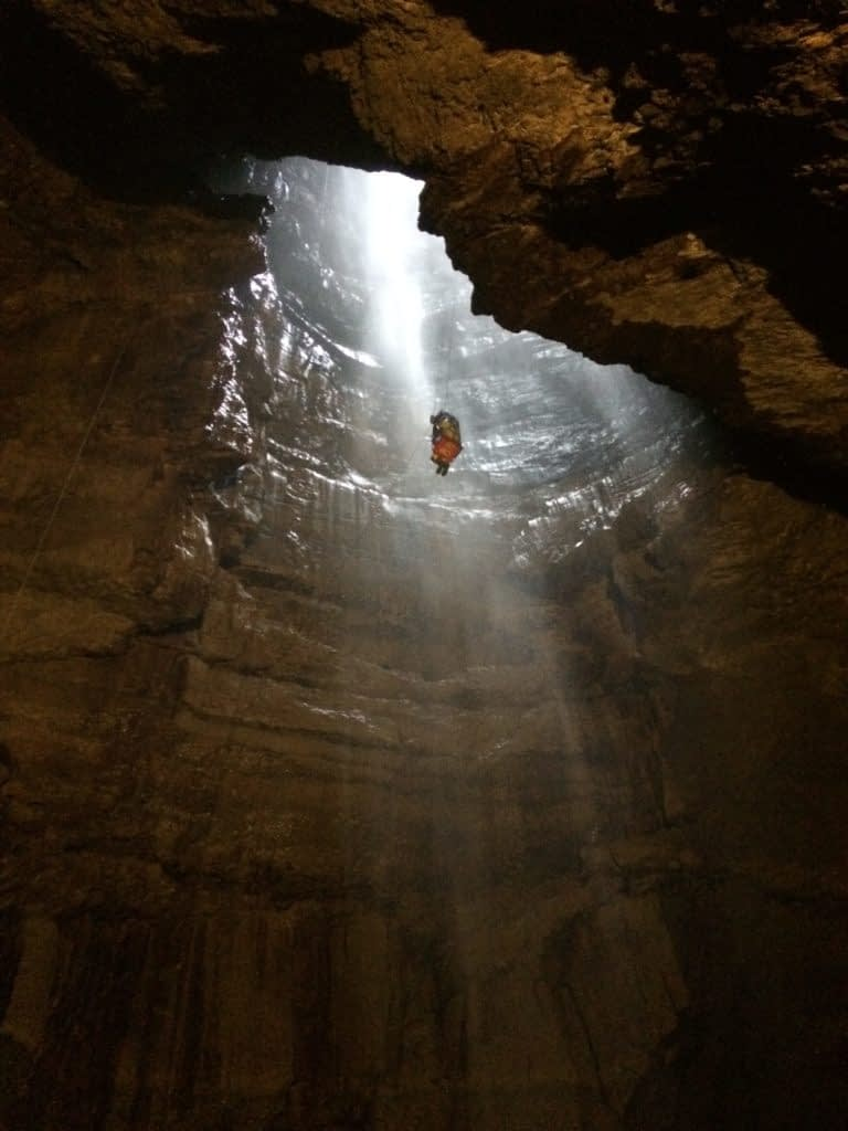 Person being lowered into cave